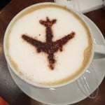 Latte with a silhouette of an airplane - More Coffee - Less Travel
