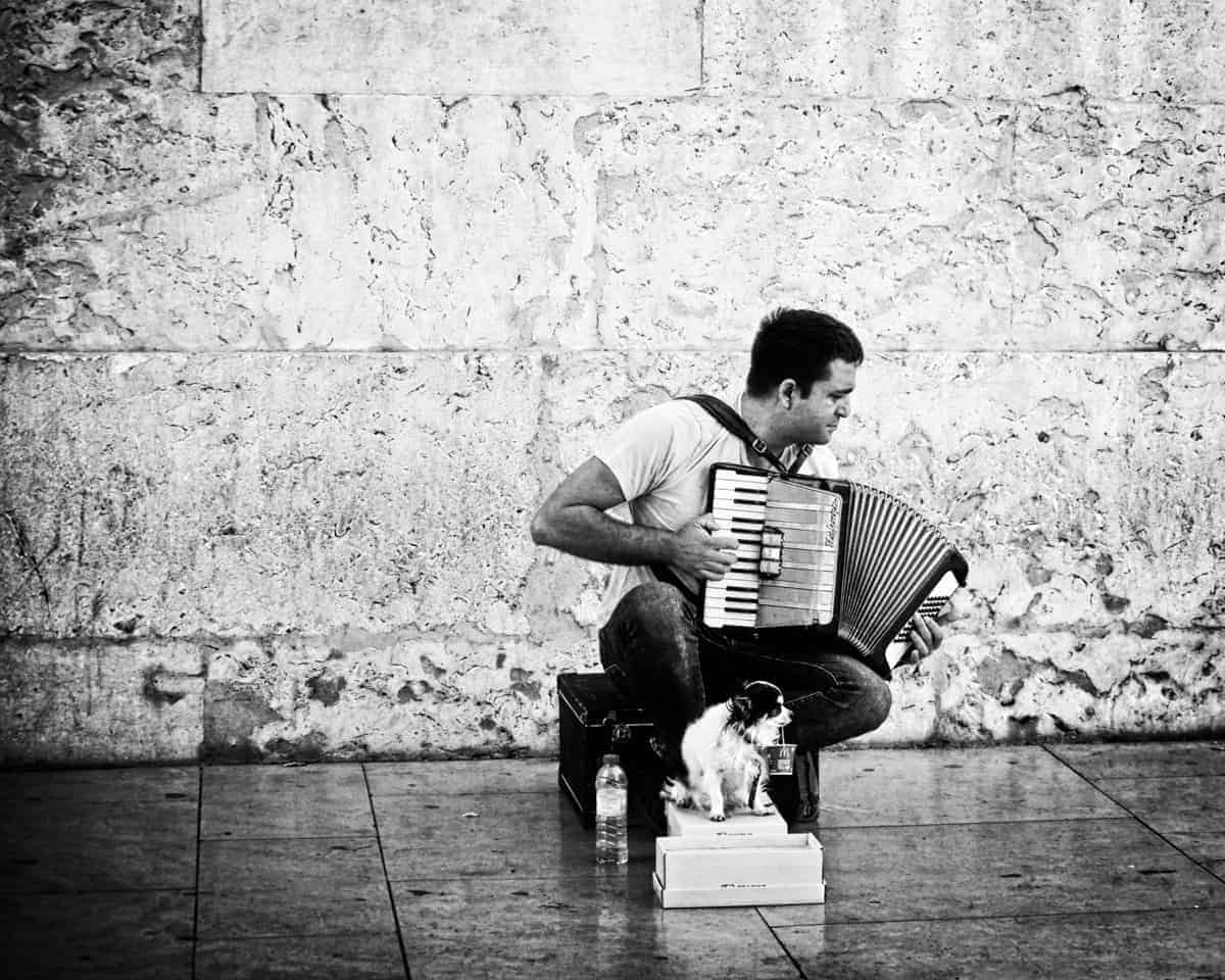 Black and white image of a lonely busker and his dog on the streets of Lisbon Portugal
