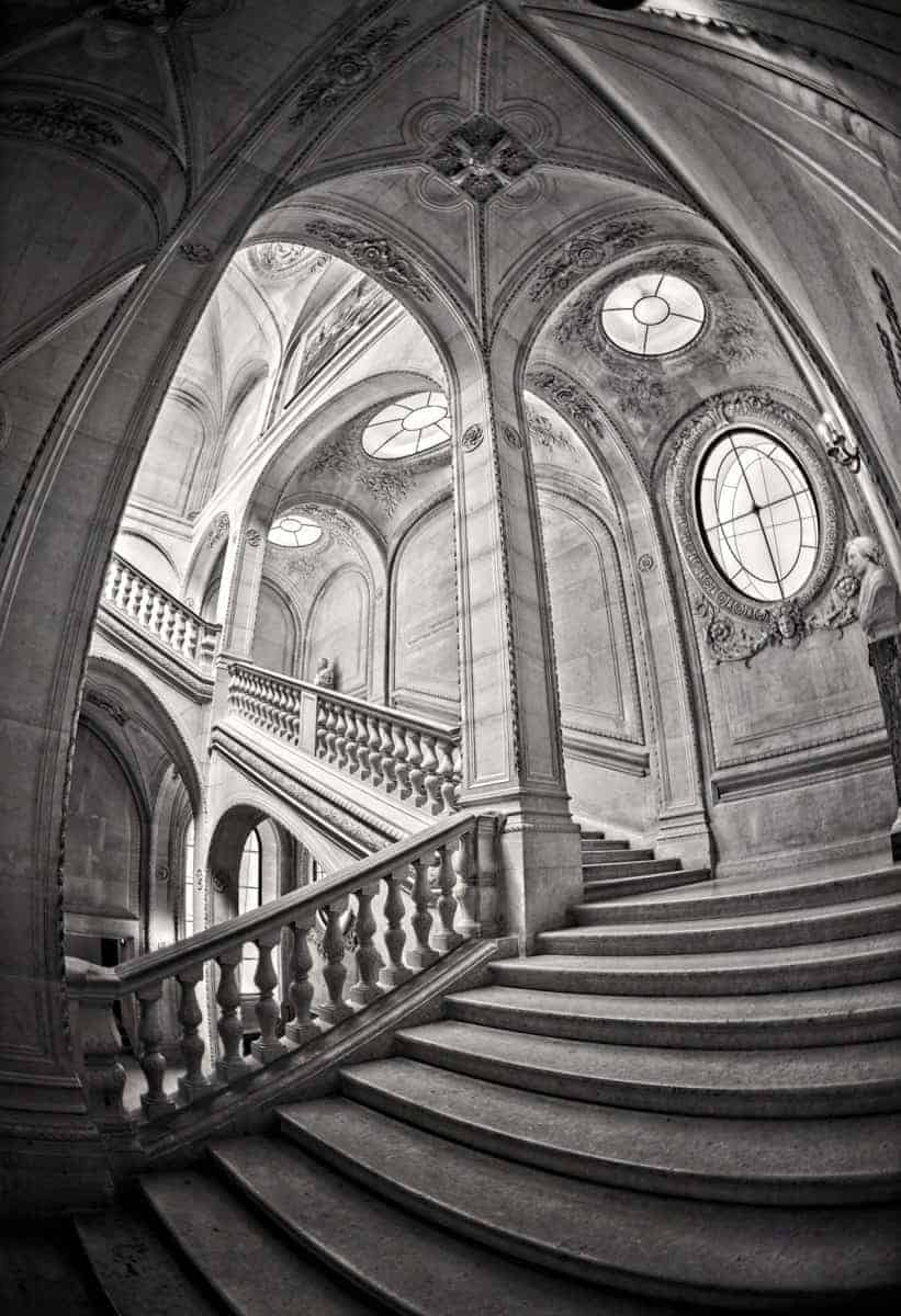 Black and white HDR image of the stairs at the Louvre Museum, feeling very Escher